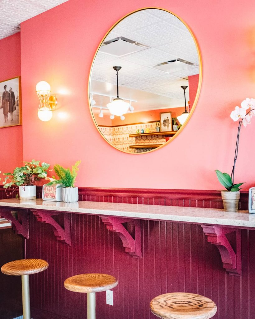 Pink wall with circular mirror at Sherry's Soda Shoppe
